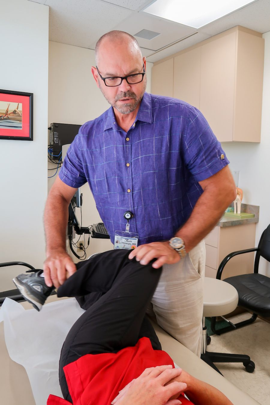 Dr. Mark Thomas examining a patient's hip mobility